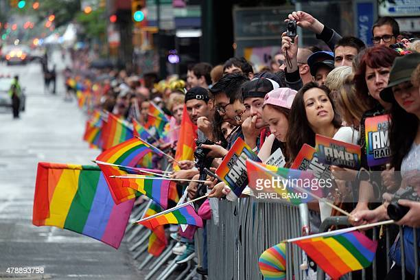 People hold rainbow flags as they wait for the start of the 2015 New York City Pride Parade in New York on June 28 2015 Under a sea of rainbow flags...