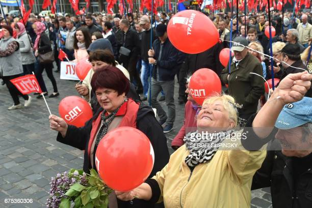 People hold red ballons during a May Day rally organised by the Ukrainian leftwing parties and the trade unions in Kiev on May 1 2017 / AFP PHOTO /...