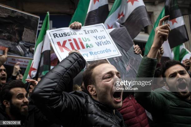 People hold signs and chant slogans during a protest against the Russian and Syrian forces bombing and blockade of the Syrian enclave of Eastern...
