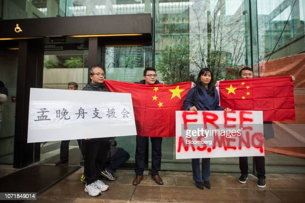 People hold signs and Chinese flags in support Meng Wanzhou chief financial officer of Huawei Technologies Co outside of a bail hearing at the...
