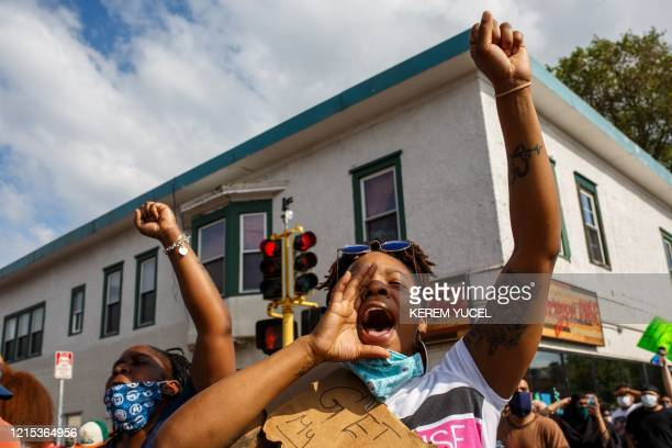TOPSHOT People hold signs and protest after a Minneapolis Police Department officer allegedly killed George Floyd on May 26 2020 in Minneapolis...