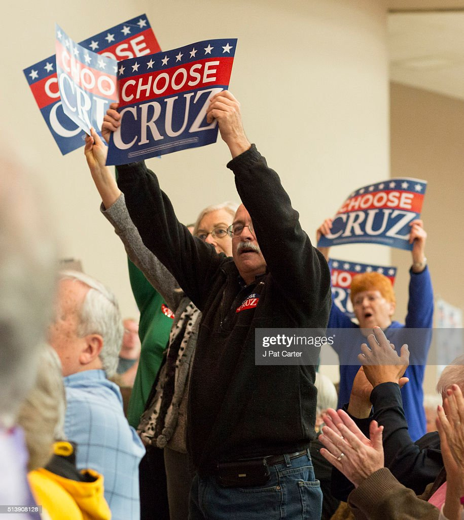 People hold signs as Republican presidential candidate Ted Cruz makes a speech at a campaign rally on March 5, 2016 in Wichita, Kansas. Cruz said he has a list of government programs that he will eliminate if elected.
