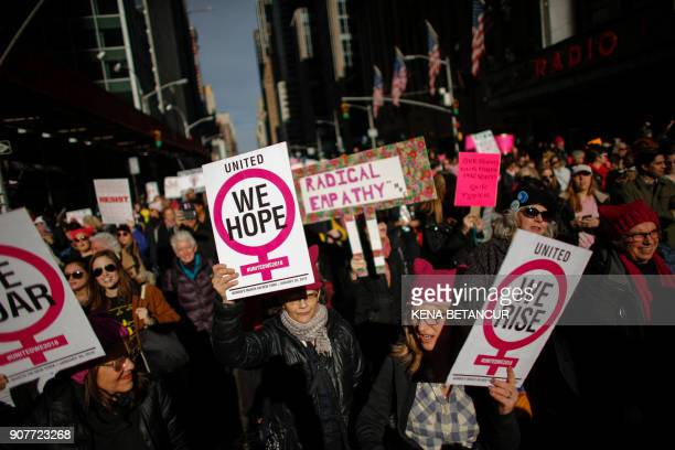 People hold signs as they attend the Womens March on New York City on January 20, 2018 in New York City. / AFP PHOTO / KENA BETANCUR