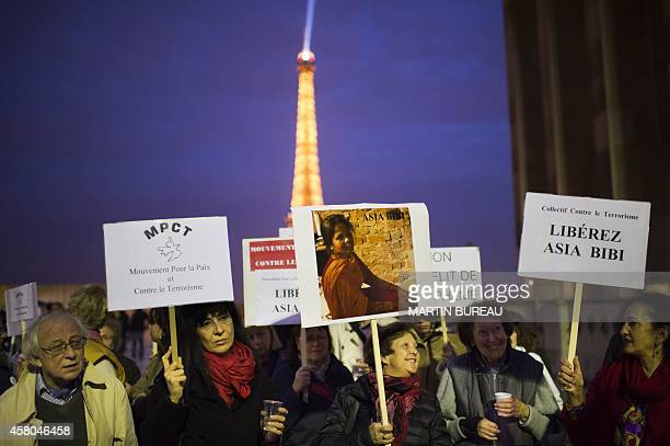 People hold signs as they demonstrate near the Eiffel Tower on the Parvis des droits de l'homme in Paris on October 29 to protest against the death...