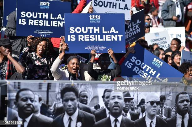 TOPSHOT People hold signs as they watch the 34th annual Kingdom Day Parade on Martin Luther King Jr Day January 21 in Los Angeles California