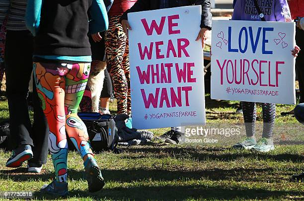 People hold signs before starting a 'Yoga Pants Parade' through a neighborhood in Barrington RI on Oct 23 2016 The parade went by the home of Alan...