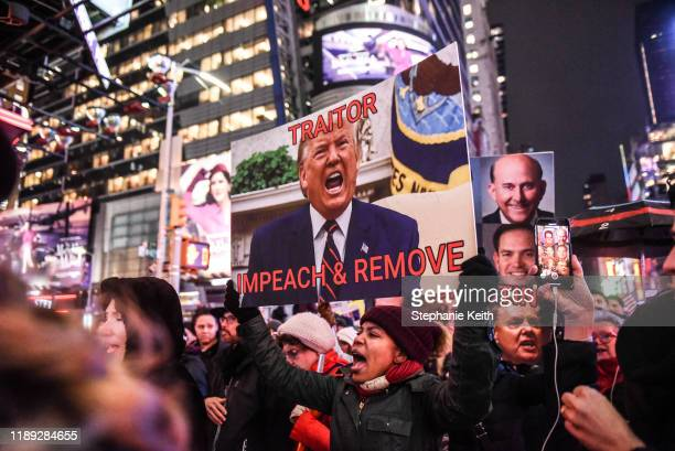People hold signs critical of US President Donald Trump while participating in a protest in support of his potential impeachment on December 17 2019...