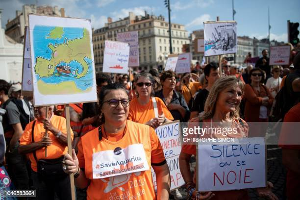 People hold signs during a demonstration in support to the Aquarius an NGO boat dedicated to the rescue of migrants at sea in Marseille's vieux port...