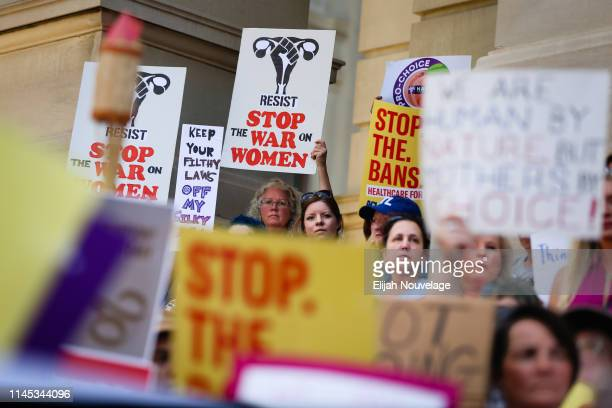 People hold signs during a protest against recently passed abortion ban bills at the Georgia State Capitol building on May 21 2019 in Atlanta Georgia...