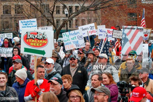People hold signs during a protest against the coronavirus shutdown in front of State Capitol in Madison Wisconsin on April 24 2020 Gyms hair salons...