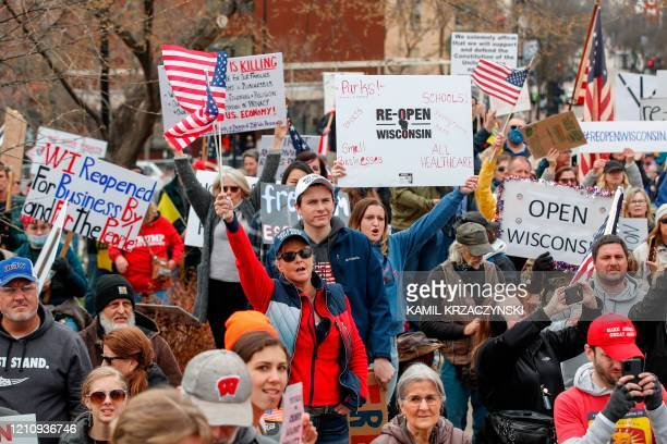 TOPSHOT People hold signs during a protest against the coronavirus shutdown in front of the State Capitol in Madison Wisconsin on April 24 2020 Gyms...