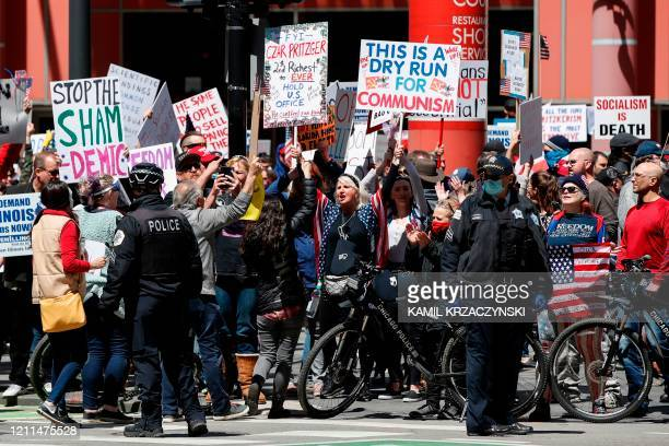 People hold signs during a protest demanding to reopen the Illinois economy, hit hard by coronavirus-related closures, in front of a James R....