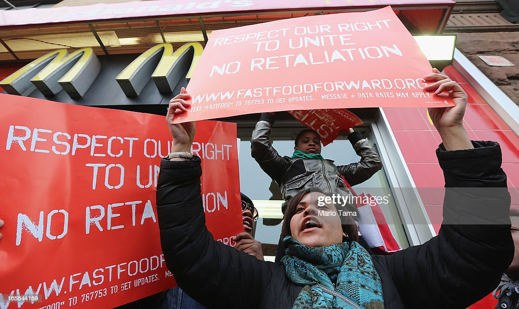 People hold signs during a protest for better wages for fast food workers outside a McDonald's restaurant in Harlem on April 4, 2013 in New York City. Organizers said hundreds of fast food workers were expected to walk off the job today from establishments including Wendy's, McDonald's and KFC to rally for better pay and union rights.