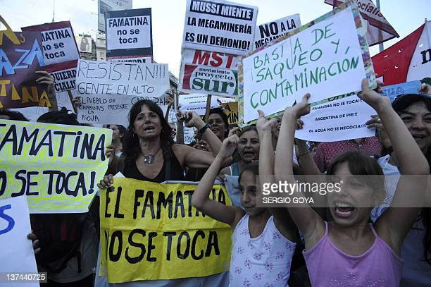 People hold signs during a protest in Buenos Aires on January 20 against openpit mining in Famatina hill in La Rioja 1222 km northwest The protest...