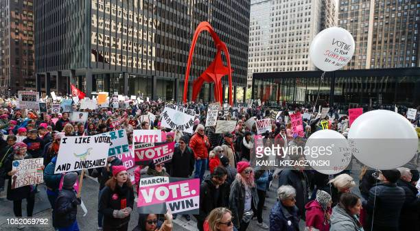 People hold signs during a rally and march on October 13, 2018 in Chicago, Illinois to inspire voter turnout ahead of midterm polls in the United...