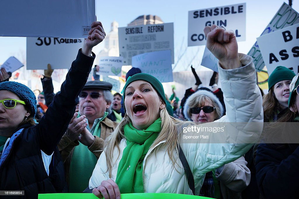 People hold signs during a rally at the Connecticut State Capital to promote gun control legislation in the wake of the December 14, 2012, school shooting in Newtown on February 14, 2013 in Hartford, Connecticut. Referred to as the 'March for Change' and held on the two-month anniversary of the massacre in Newtown, Connecticut, participants called for improved gun safety laws. Among the safety measures being demanded are for universal background checks, more work within the mental health community and restricting high-capacity magazines.