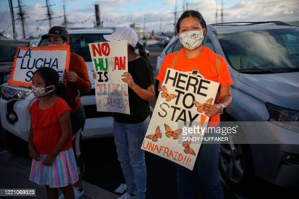 People hold signs during a rally in support of the Supreme Court's ruling in favor of the Deferred Action for Childhood Arrivals program in San Diego...