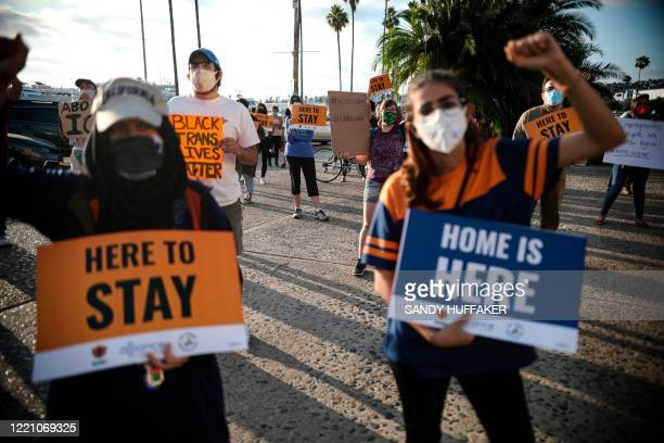 People hold signs during a rally in support of the Supreme Court's ruling in favor of the Deferred Action for Childhood Arrivals program, in San...
