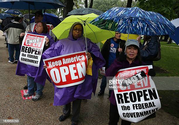 People hold signs during a rally to urge Congress to end the government shutdown at the US Capitol October 9 2013 in Washington DC The US government...