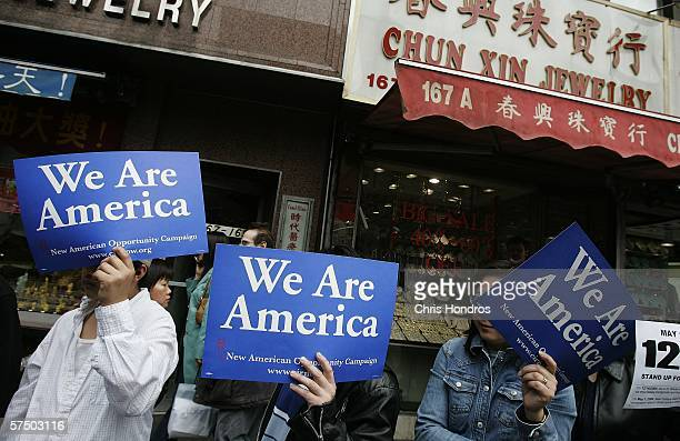 People hold signs during a sidewalk rally against proposed crackdowns on illegal immigrants May 1 2006 in Chinatown in New York Immigrants and their...