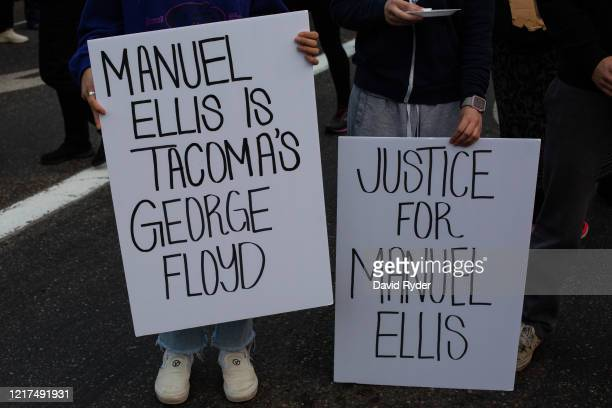 People hold signs during a vigil for Manuel Ellis a black man whose March death while in Tacoma Police custody was recently found to be a homicide...