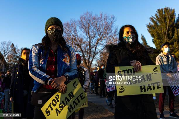 """People hold signs during the """"Asian Solidarity March"""" rally against anti-Asian hate in response to recent anti-Asian crime on March 18, 2021 in..."""