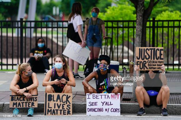 People hold signs following a protest against police brutality on June 6 2020 in Atlanta Georgia This is the 12th day of protests since George Floyd...