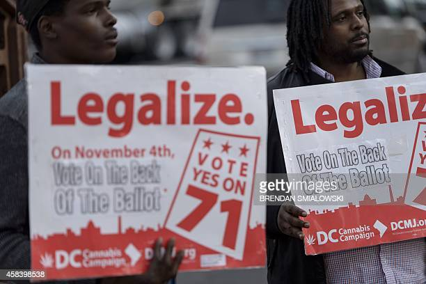 People hold signs for Ballot Initiative, the legalization of marijuana, on November 4, 2014 in Washington, DC. Voters around the United States went...