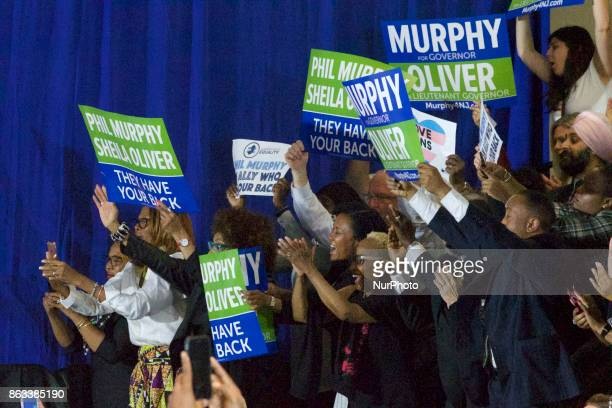 People hold signs in support of Democratic candidate Phil Murphy who is running against Republican Lt Gov Kim Guadagno for the governor of New Jersey...