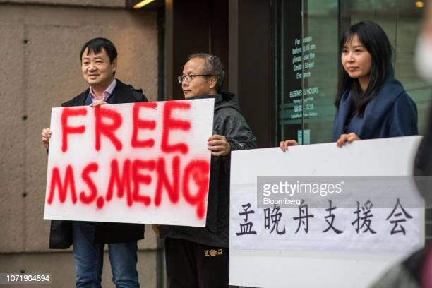 People hold signs in support of Meng Wanzhou chief financial officer of Huawei Technologies Co outside of a bail hearing at the Supreme Court in...