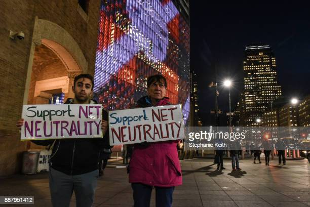 People hold signs in support of net neutrality in front of Verizon's headquarters on December 7 2017 in New York United States People are protesting...