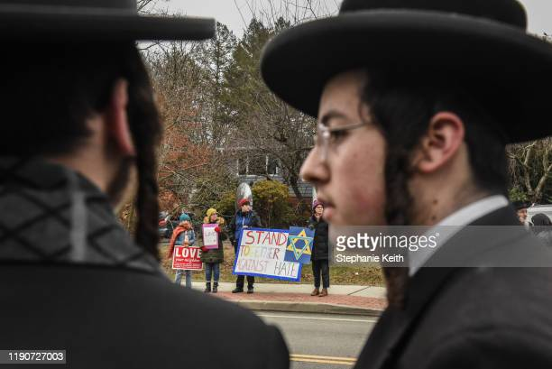 People hold signs of support near the house of Rabbi Chaim Rottenberg on December 29 2019 in Monsey New York Five people were injured in a knife...