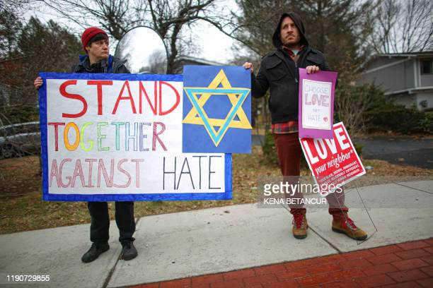 TOPSHOT People hold signs of support near the house of Rabbi Chaim Rottenberg on December 29 2019 in Monsey New York An intruder stabbed and wounded...