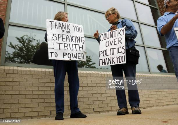 People hold signs outside a town hall event with Representative Justin Amash, a Republican from Michigan, not pictured, in Grand Rapids, Michigan,...