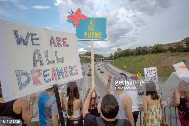 People hold signs over the 110 freeway as thousands of immigrants and supporters join the Defend DACA March to oppose the President Trump order to...