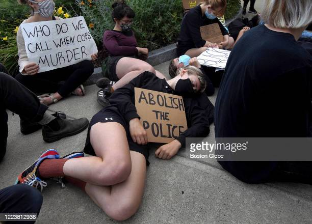 """People hold signs reading """"abolish the police"""" and """"who do we call when cops murder"""" during a Solidarity for Black Lives Rally in Boston's Brighton..."""