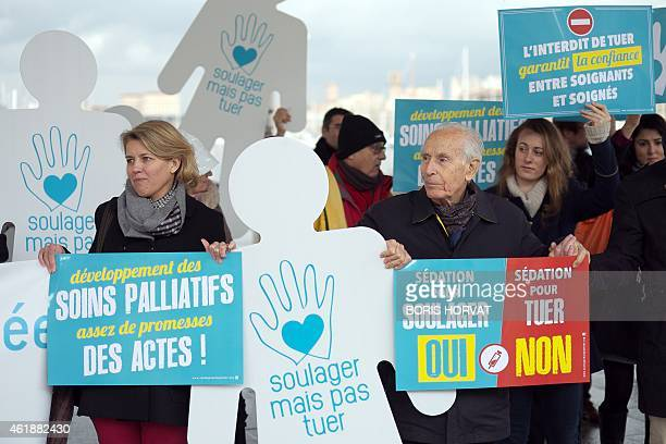 People hold signs reading ''Development of palliative care enough promises acts'' ''Bring relief but do not kill' and ''sedation to relief Yes...