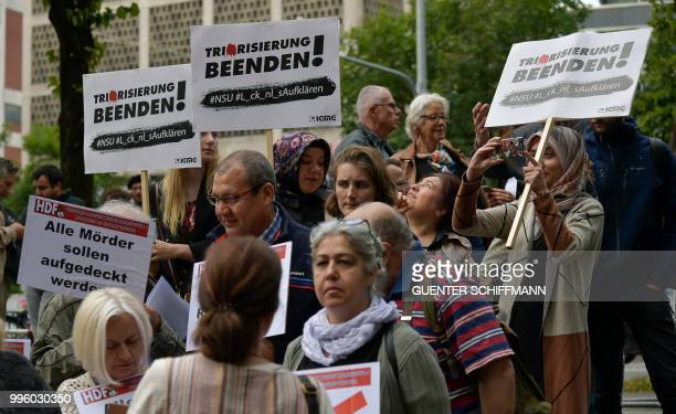 People hold signs reading 'end terrorism' near the regional court in Munich before the proclamation of sentence in the trial against Beate Zschaepe...