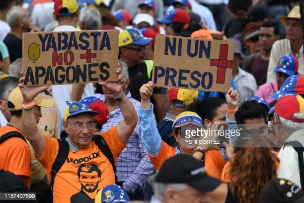 People hold signs reading Enough of blackouts and Not one more prisoner before a session of the oppositionled National Assembly at Alfredo Sadel...