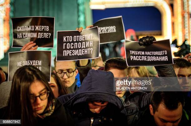 TOPSHOT People hold signs reading 'How many victimes actually' 'Who is going to answer Mr President' 'We demand a real investigation' during an...