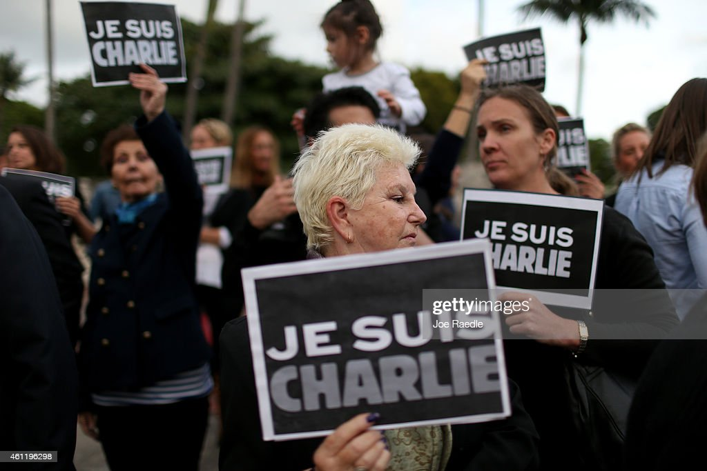 People hold signs reading 'Je Suis Charlie' (I am Charlie), to show their support for the victims of the terrorist attack at French magazine Charlie Hebdo on January 8, 2015 in Miami. Gunmen in Paris, France killed 12 people during an attack at the offices of the satirical newspaper on January 7, 2015.