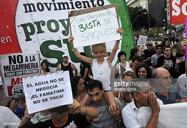 People hold signs reading 'Mrs President Enough of sacking' and 'Water is not negotiable The Famatina will not be touched' during a protest in Buenos...