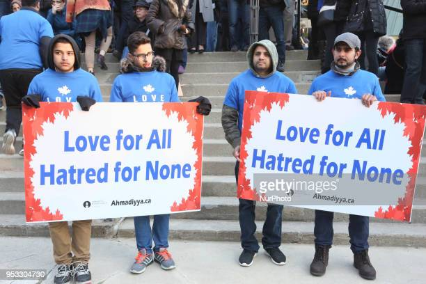 People hold signs saying 'Love for all hatred for none' as thousands of people attended an interfaith vigil at Nathan Phillips Square in memory of...