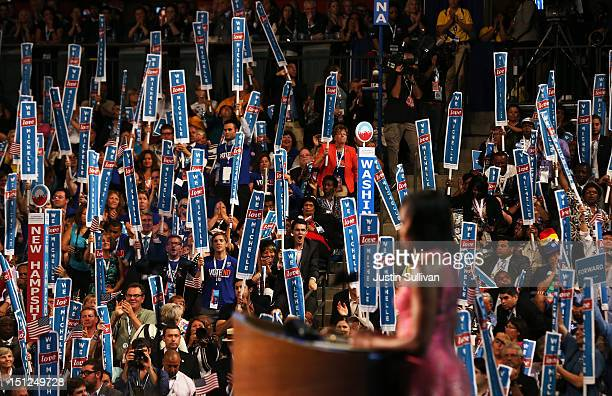 """People hold signs that read """"We Love Michelle"""" as First lady Michelle Obama speaks on stage during day one of the Democratic National Convention at..."""