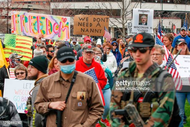 People hold signs while others carry weapons during a protest against the coronavirus shutdown in front of State Capitol in Madison Wisconsin on...
