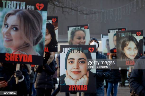 People hold signs with images of the victims of the downed Ukraine International Airlines flight PS752, which was shot down near Tehran by Iran's...