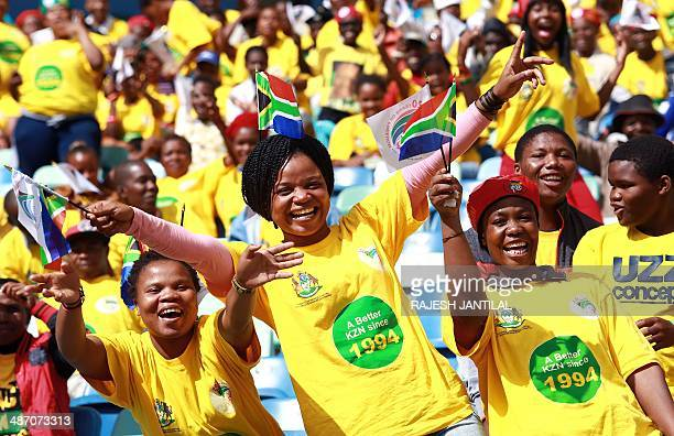 People hold small South African flags as they take part in the 20th Freedom Day celebrations at the Moses Mabhida Football stadium in Durban on April...