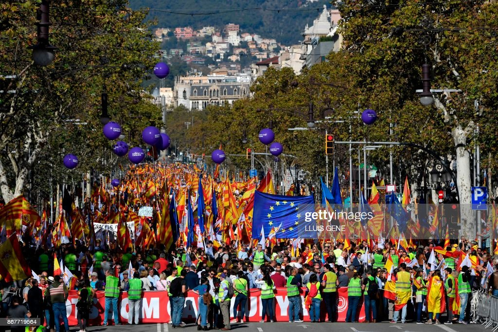 People hold Spanish, Catalan Senyera and EU flags during a pro-unity demonstration in Barcelona on October 29, 2017. Pro-unity protesters were to gather in Catalonia's capital Barcelona, two days after lawmakers voted to split the wealthy region from Spain, plunging the country into an unprecedented political crisis. /