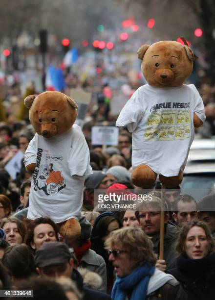 People hold teddy bears wearing tshirst depecting Charlie Hebdo cartoons during a Unity rally Marche Republicaine on January 11 2015 at the Place de...