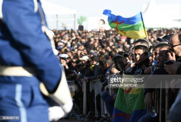 People hold the Amazigh flag as thousands of mourners attend the funeral procession and burial of Hocine AitAhmed one of the fathers of Algeria's...
